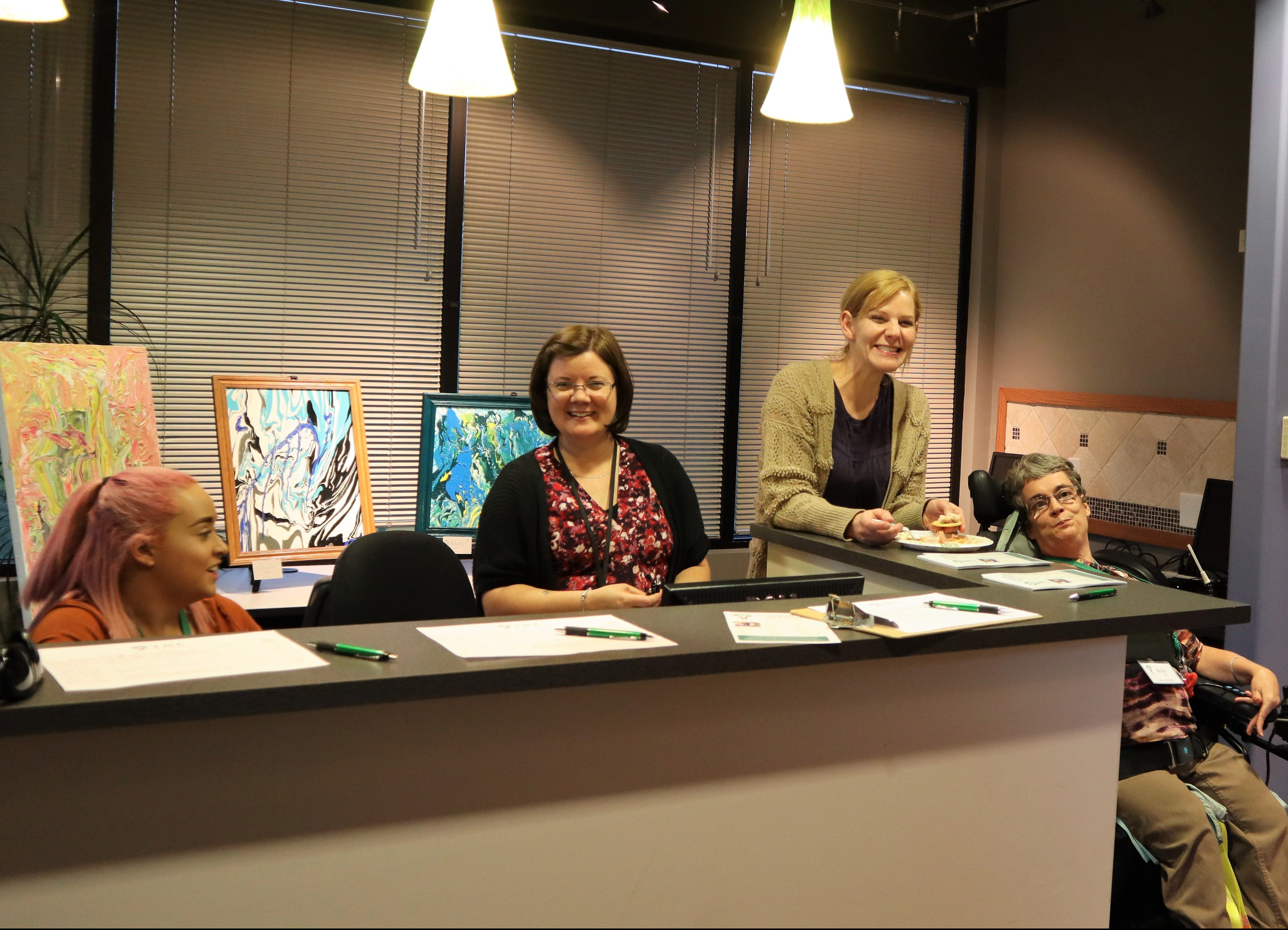 people smiling at a desk to greet guests of the Art Show
